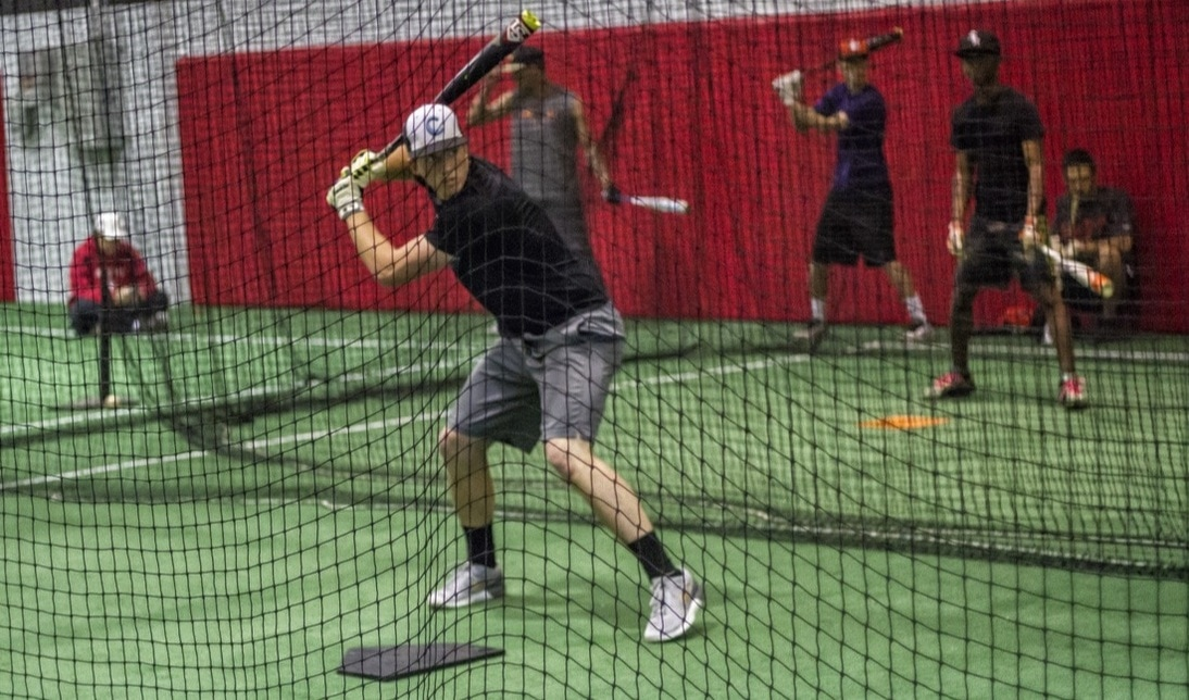 Players practising in baseball training nets